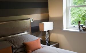 Horizontal striped wallpaper sits behind a bespoke fauz croc skin headboard